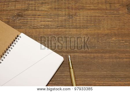 Open Spiral Bound Notebook With White Pages And Gold Pen.