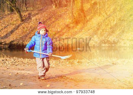 little boy digging in autumn park