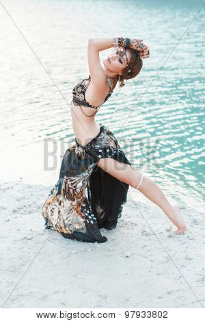 Beautiful Girl Dancing In Tribal Style On White Sand Beach Near The Water