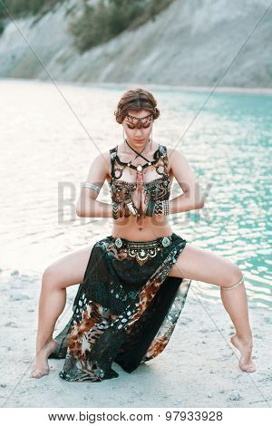 Beautiful Girl In Tribal Fusion Costume Standing In A Pose On The Banks Of The Beach, Background Of