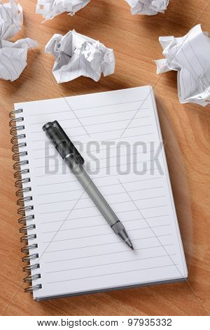 Closeup of an ink pen on a pad of paper with crumpled wads of paper in the background.