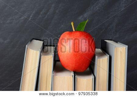 A red apple perched atop text books on a teachers desk with an out of focus chalkboard behind.