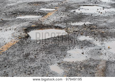 Puddles on old cracked road