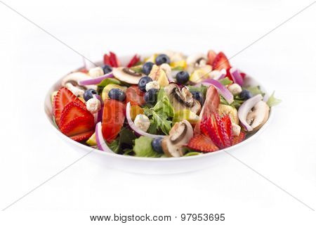 Detail of fresh colorful salad with healthy ingredients, berries, figs, greens and feta cheese