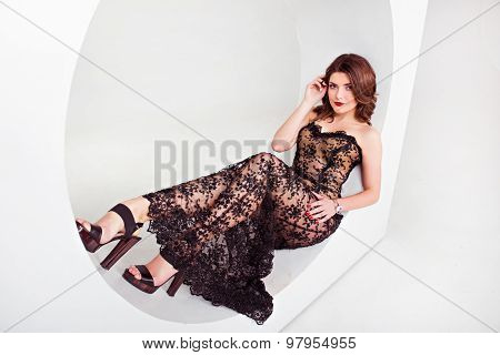 Girl Dressed In A Dress Of Black Openwork Sitting On The Windowsill Of The Round Form