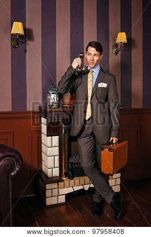Businessman Giving Instructions Over The Phone, Holding A Suitcase.