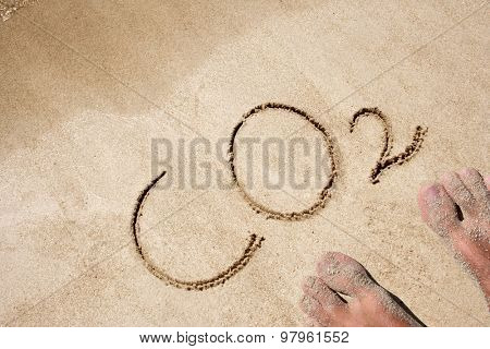 CO2 or water hand written in sand on a beach on an exotic island background with feet