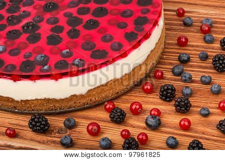 Cheesecake with jell, red currants, blueberries and blackberries on the wooden background.