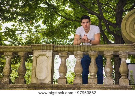 Handsome young man standing on a balcony or bridge