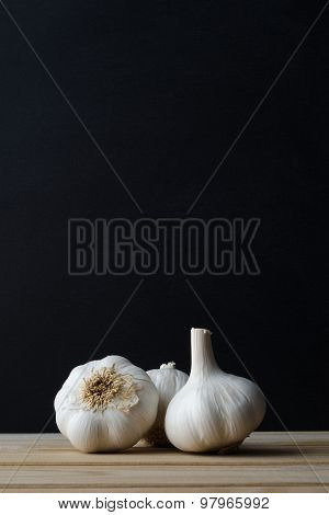 Garlic Bulbs  On Wood Plank Table With Black Background