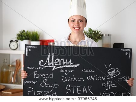 Chef woman holding the menu board , standing in kitchen