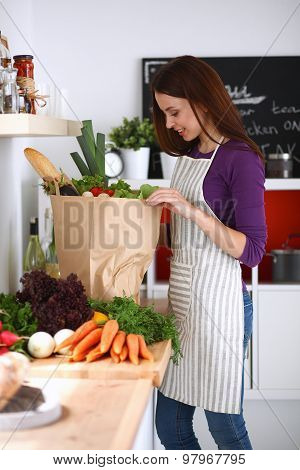 Young woman standing in her kitchen near desk with  grocery shopping bags
