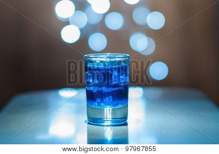 Glass with alcohol drink on wooden background, copyspace. An old vintage countertop highlight and a