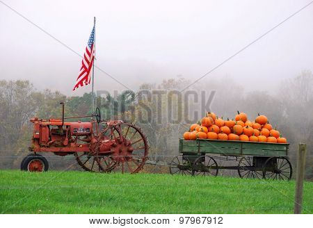 Vintage tractor, american flag and wagon full of pumpkins