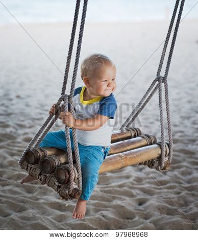 Baby sitting on a bamboo swing