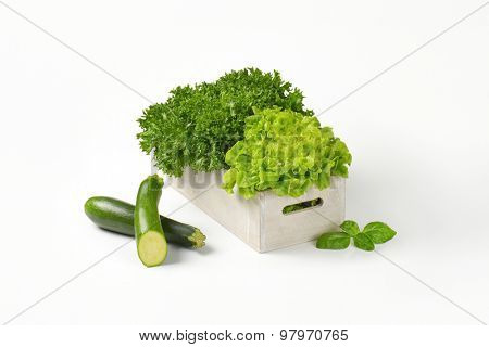 box of lettuce and courgette on white background