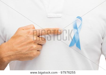 medicine, health care, gesture and people concept - close up of male hand pointing to blue prostate cancer awareness ribbon on his chest