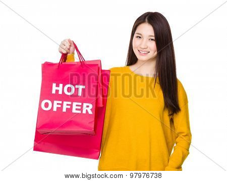 Woman hold with red shopping bag and showing hot offer