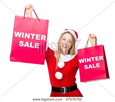 Woman with christmas party dress hold up with shopping bag and showing winter sale