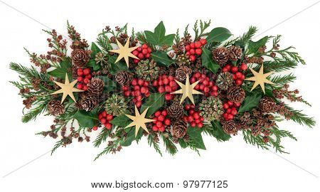 Christmas gold star decorations, holly, mistletoe, ivy, pine cones and traditional greenery over white background.