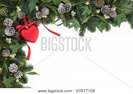 Christmas background border with red heart bauble decoration, holly, ivy, mistletoe, pine cones and blue spruce fir over white.
