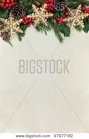 Christmas abstract background border with gold snowflake decorations, holly, fir and cedar cypress greenery over parchment paper.
