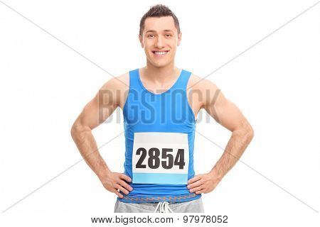Young male runner in a blue jersey with a race number on his chest isolated on white background