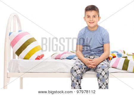 Boy in blue pajamas sitting on a bed and looking at the camera isolated on white
