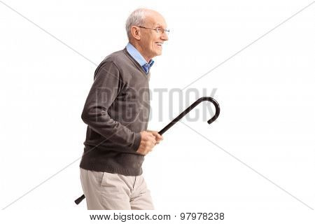 Joyful senior gentleman carrying a cane in his hand and running isolated on white background