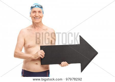 Senior man in a black swim trunks holding a big black arrow pointing right and looking at the camera isolated on white background