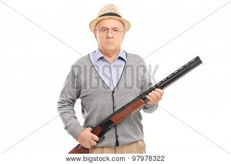 Serious senior gentleman holding a shotgun and looking at the camera isolated on white background