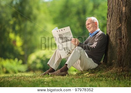 Cheerful senior gentleman reading a newspaper in park and leaning against a tree seated on the ground on beautiful summer day