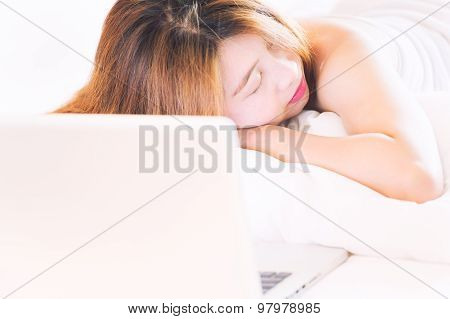 Beautiful Young Woman In Bathrobe Fallen Asleep While Using Laptop In Bed