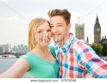 travel, vacation, technology and friendship concept - happy couple taking selfie over big ben and thames river in london background