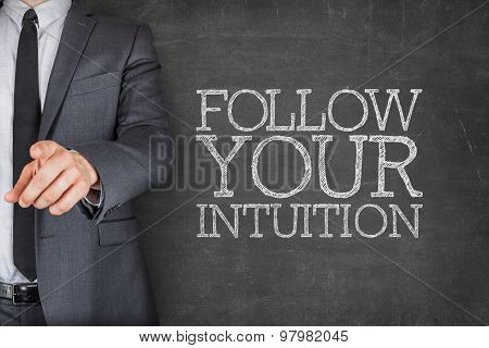 Follow your intuition on blackboard with businessman
