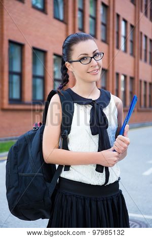 Girl In School Uniform With Backpack Standing In Campus