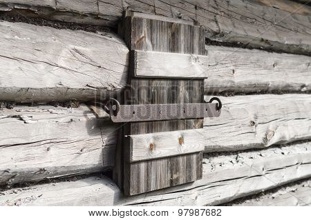 Closed Wooden Shutter On Aged Wall Of Log Cabin