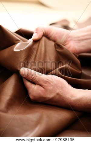 Hands tailor to check the quality of the material
