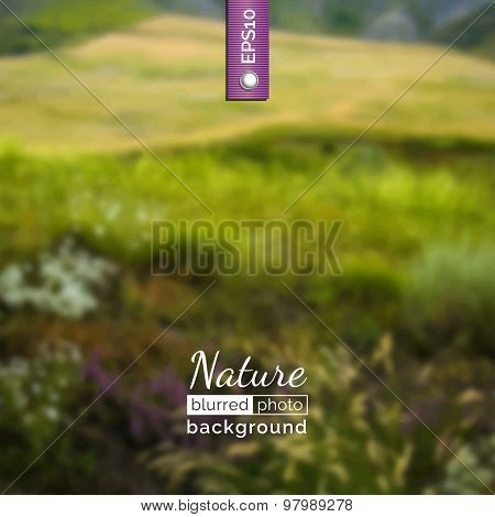 Blurred photo background with green hills.