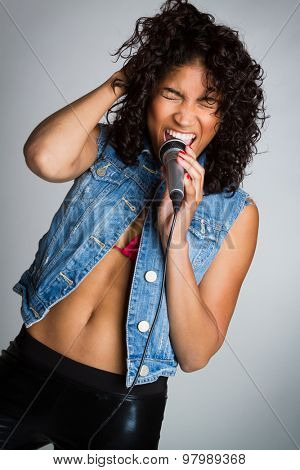 Black music rockstar woman singing into microphone