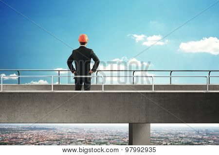back view of businessman in formal wear and orange hard hat standing on concrete bridge and looking into the distance