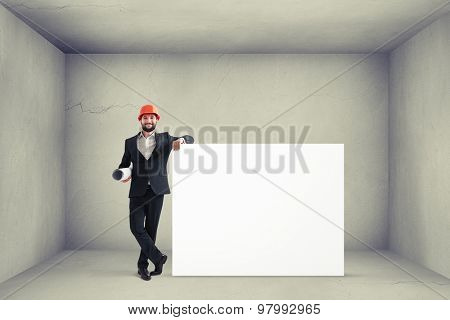 smiley businessman in formal wear and orange helmet holding big empty white banner in grey concrete room