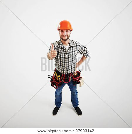 view from above of smiley builder in hard hat and belt with tools looking up and showing thumbs up. isolated on light grey background