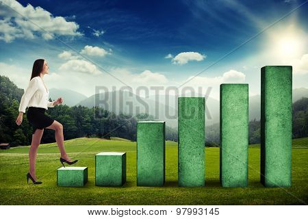 happy businesswoman walking up to the top of concrete diagram over beautiful landscape with forest, hills and sky