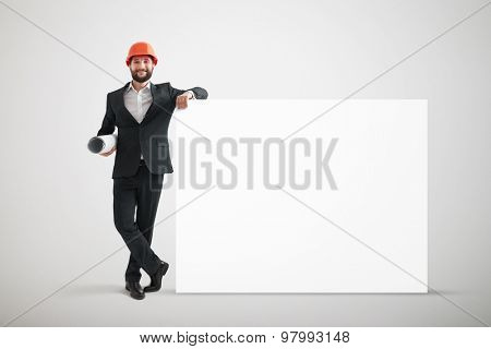 smiley businessman in formal wear and orange helmet holding big empty white banner over grey background