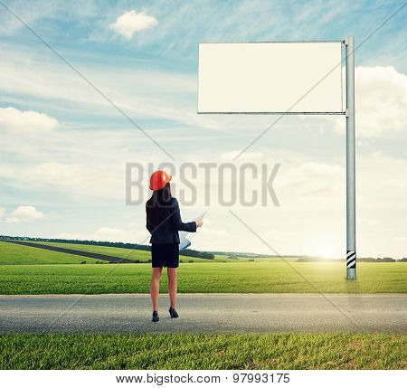 back view of constructor woman with blueprint looking at empty big billboard at outdoor