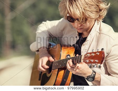 Young Man Playing On Guitar Portrait