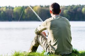 stock photo of rod  - Angler sitting in grass at lake fishing with his rod - JPG