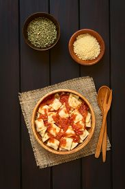 foto of grating  - Cooked ravioli with homemade tomato sauce in wooden bowl with grated cheese and dried oregano in small bowls wooden spoon and fork on the side photographed overhead on dark wood with natural light - JPG