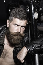 foto of moustache  - Portrait of serious sexy unshaven man with beard and handlebar moustache in black leather biker jacket with bare torso sitting near motorcycle looking forward vertical picture - JPG